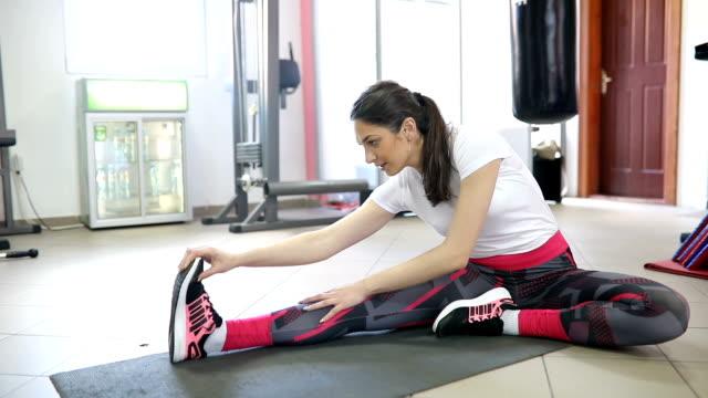Attraktiv ung kvinna gör plankan övning medan du tränar i gymmet