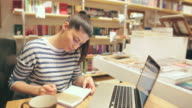 Attractive young woman working on the laptop in the bookstore