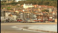 EXT Seagulls flying and landing on beach General View Beach with seafront houses behind Close Shot Flashing lights outside amusement arcade Low Angle...
