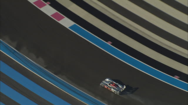 AERIAL Audi diesel racing car driving on race track with red and blue stripes/ Cote d'Azur, France