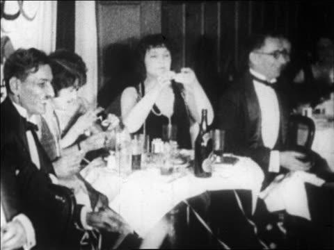 B/W 1928 audience at table in nightclub throwing streamers / newsreel