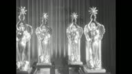 Audience Awards statuettes on table at Beverly Hilton Hotel / WS people seated at dinner tables / Natalie Wood accepts Audience Award statuetteAudie...