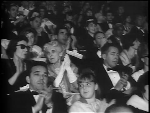 B/W 1964 audience in formalwear clapping at Academy Awards / newsreel