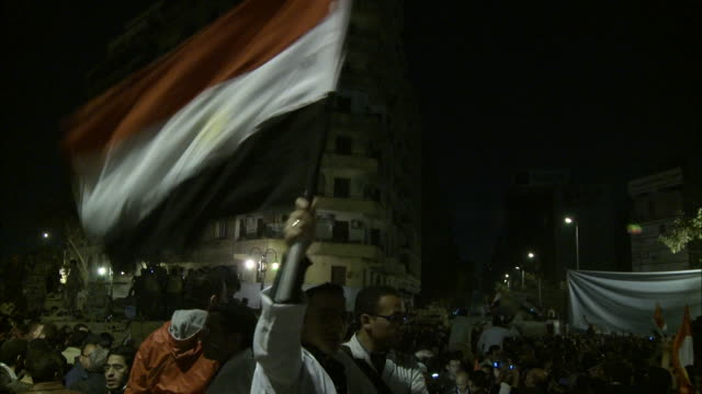 Audience member in Tahrir Square waving Egyptian flag in front of a bustling crowd who are waving fists in the air during Mubarak's Speech / Cairo...