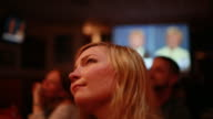 Audience members at a debate watching party organized by the Democratic Party watch listen and react as Hillary Clinton and Donald Trump face off in...