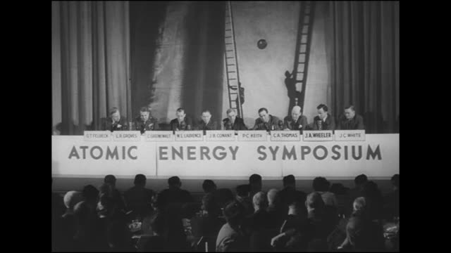 Stage w/ men seated behind sign 'Atomic Energy Symposium' audience seated FG SOT Conant saying nuclear power not to replace electrical in US LR...