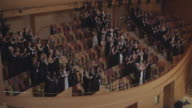 MS Audience standing and applauding in formal attire in various sections of concert hall