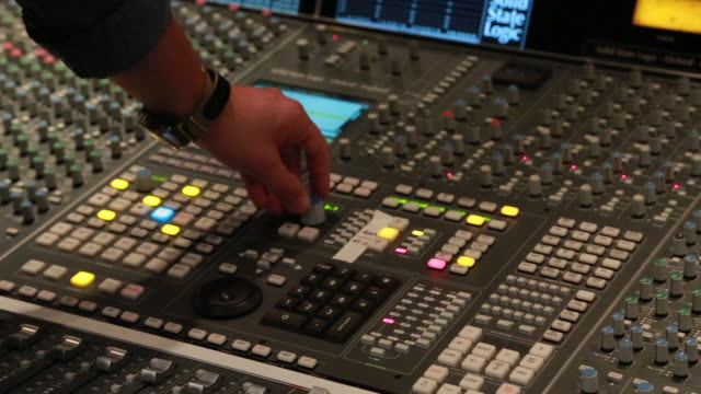 Audio engineer adjusting audio console