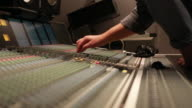Audio Engineer adjusting knobs on console, low angle