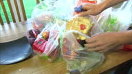 Audio levels in this clip have been loweredCLEAN Interior shots of a mother and father with two young children unpacking plastic shopping bags and...