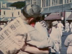 August 14 1945 man and woman kissing in VJ Day parade/ woman holding newspaper with peace headline