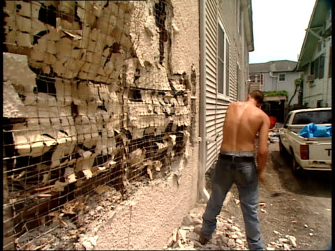 August 16 2006 MONTAGE Man sledgehammering exterior wall of house / New Orleans Louisiana United States