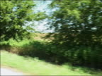 August 17 2005 Medium shot side car point of view driving along road past police blockade / Crawford Texas / AUDIO
