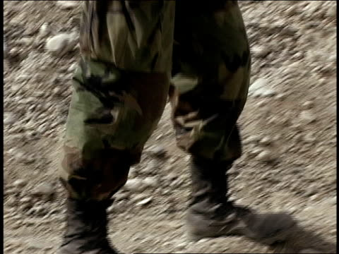August 2004 Closeup pan Afghan National Army soldier wearing dusty boots stands in front of army barracks/ Afghanistan