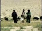 August 2004 Medium shot Three Afghan shepherds standing in field in front of their flock/ Afghanistan
