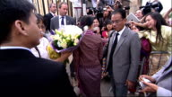 Aung San Suu Kyi arrives in Oxford ENGLAND Oxford EXT Motorcade arrives headed by police bikes / 4WD arrives and Aung San Suu Kyi steps out waves...