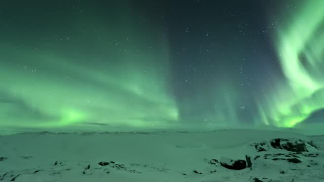 T/L of aurora on frozen ridge in Arctic