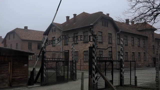 Holocaust memorial ceremony POLAND Auschwitz EXT 'Arbeit Macht Frei' on entrrance to Auschwitz Concentration Camp and crane shot over camp buildings