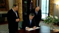 Gordon Brown signs book of condolence ENGLAND London Australia House INT Gordon Brown MP into room and signs book of condolence to victims of recent...