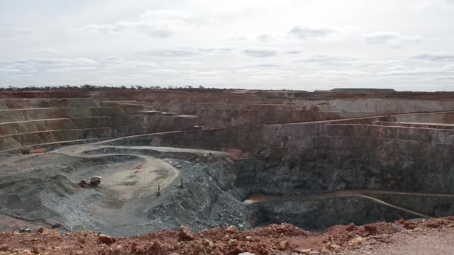 Wide shot wide shot a dump truck loaded with ore drives along a haul road in the open pit mine Wide shot vehicles and machinery operate in the open...