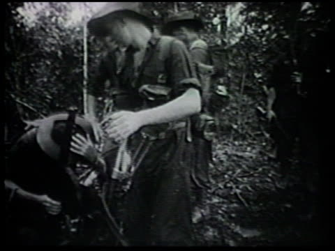 Australian Imperial Forces 'The Diggers' 7th Division stopping in forested area of Owen Stanley Range soldiers setting up camp tents eating looking...