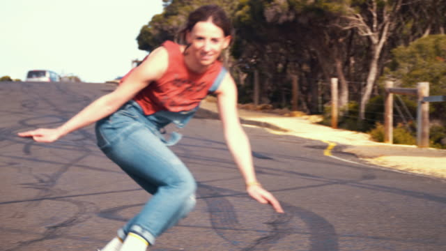 Australian Locals in Sport: female longboard skater riding in an empty road