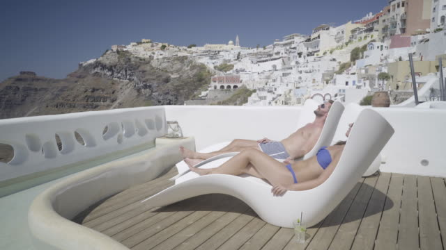 authentic wealth - couple relaxing on private porch in santorini