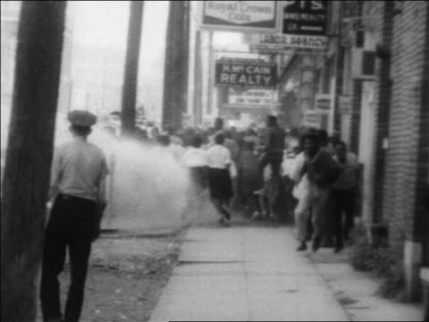 B/W 1963 authorities hosing demonstrators on sidewalk in civil rights riot / Alabama / newsreel