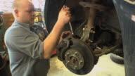 CU TD Auto mechanic adjusting vehicle's brake pad assembly at auto repair shop / Chelsea, Michigan, USA