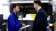 Auto mechanic and customer in auto repair shop