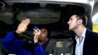 Meccanico d'auto e cliente nel negozio di riparazione auto
