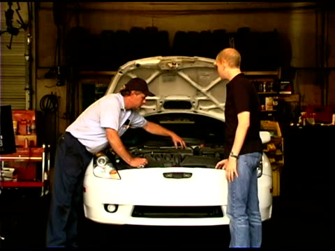 Auto mechanic and young man by car
