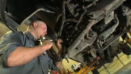 CU Auto mechanic uses hammer to help remove drive cotter pin from the vehicle's undercarriage at auto repair shop / Chelsea, Michigan, USA