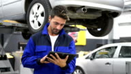 Auto mechanic using a digital tablet