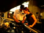 Auto mechanic with woman by car