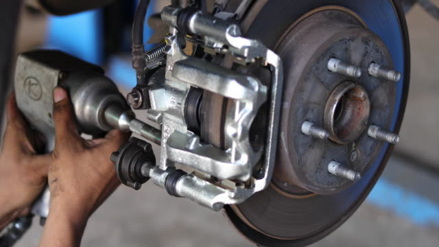 Auto mechanic working on car wheel brake disc and shoes of lifted automobile at repair service station