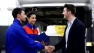 Auto mechanics and customer in auto repair shop