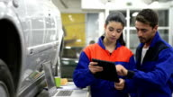 Auto mechanics working with digital technologies