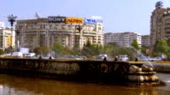 MS PAN Automobile traffic flowing around  fountain with communist era apartment buildings all around / Bucharest, Romania