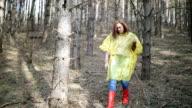 Autumn female in raincoat walking a forest