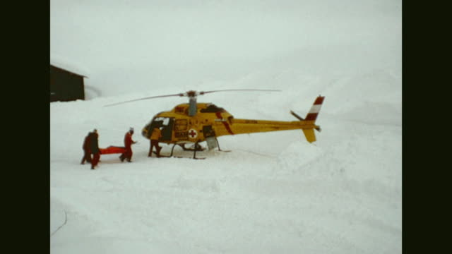 avalanche destroyed parts of the village two snow crawlers plowing snow in the village rescue helicopter landing emergency services carrying injured...