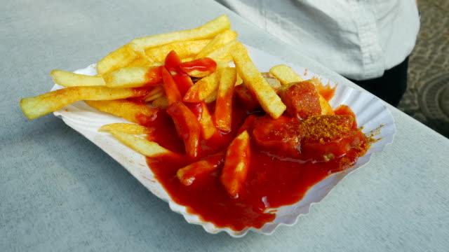 Durchschnittliche Frau isst Currywurst und Pommes frites (4 k UHD zu/HD)