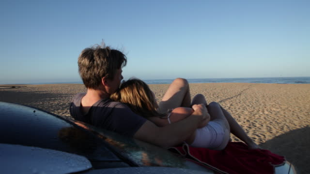PAN away from couple relaxing embracing on bonnet of car on beach in morning/Tarifa/Andalucia/Spain