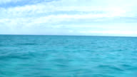 Azure tropical sea with cloudy sky from moving boat