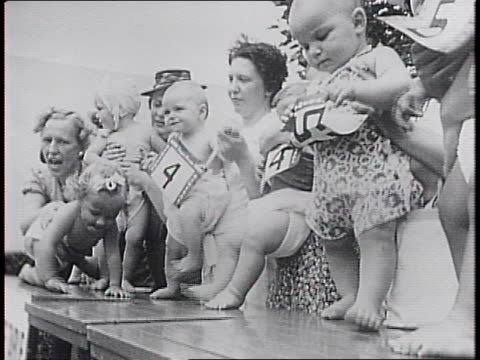 Babies with numbers on their chests stood on table top by their mothers / closeups of babies / line of mothers behind a derby banner lean over and...