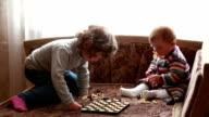 Baby och hennes syster leker med schackpjäser
