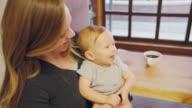 Baby und Mama in einem Cafe
