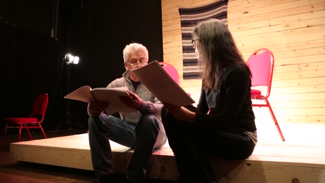 Baby boomer actors rehearsing their lines for a theatrical play