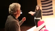 Baby boomer director giving direction to female actors rehearsing their lines for a theatrical play
