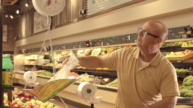 TS baby boomer man in produce section of grocery store picking limes and placing bag on weighing scale